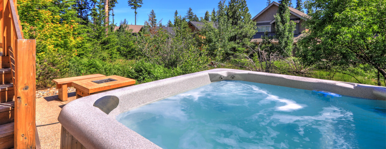 Perfectly manicured backyard boasts modern hot tub for quiet relaxation