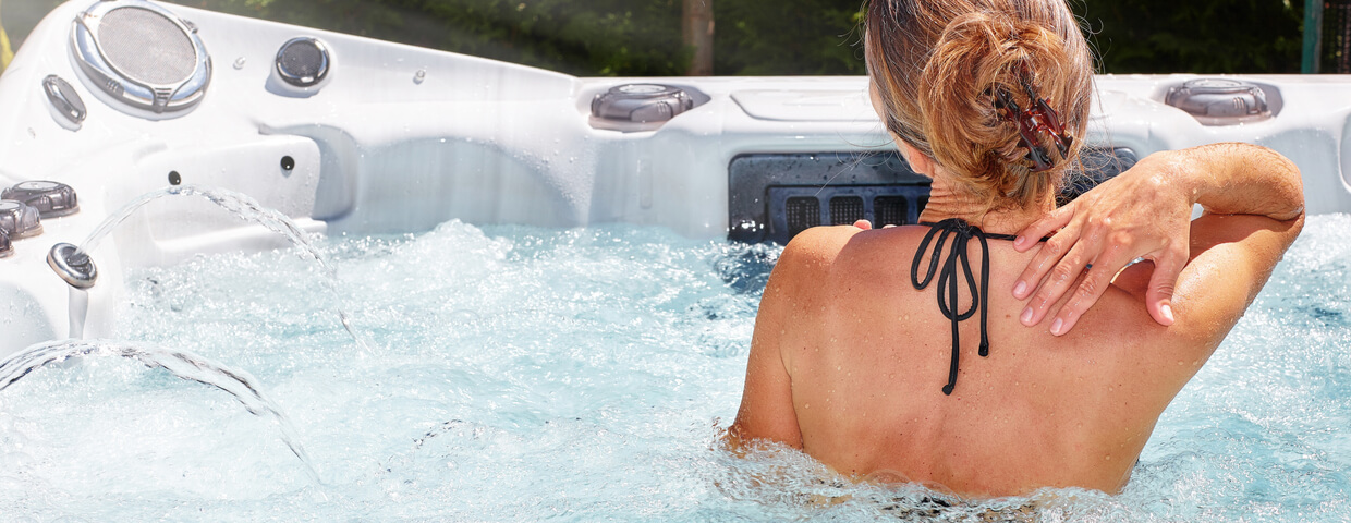 back view of a woman in a hot tub or spa, jets are going, relaxing in the spa