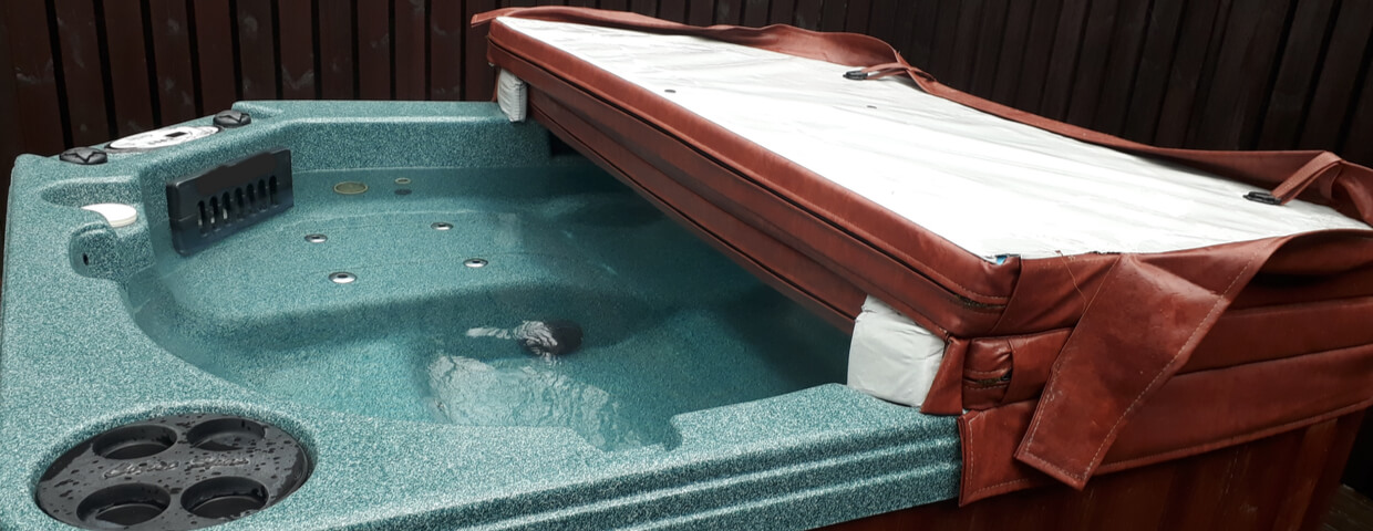 hot tub with a cover halfway open, importance of a hot tub or spa cover concept